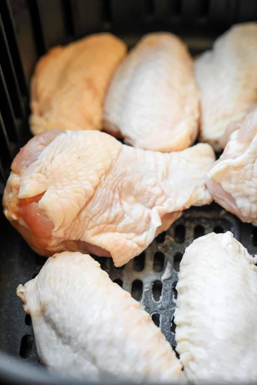 Raw chicken wings in an air fryer basket.
