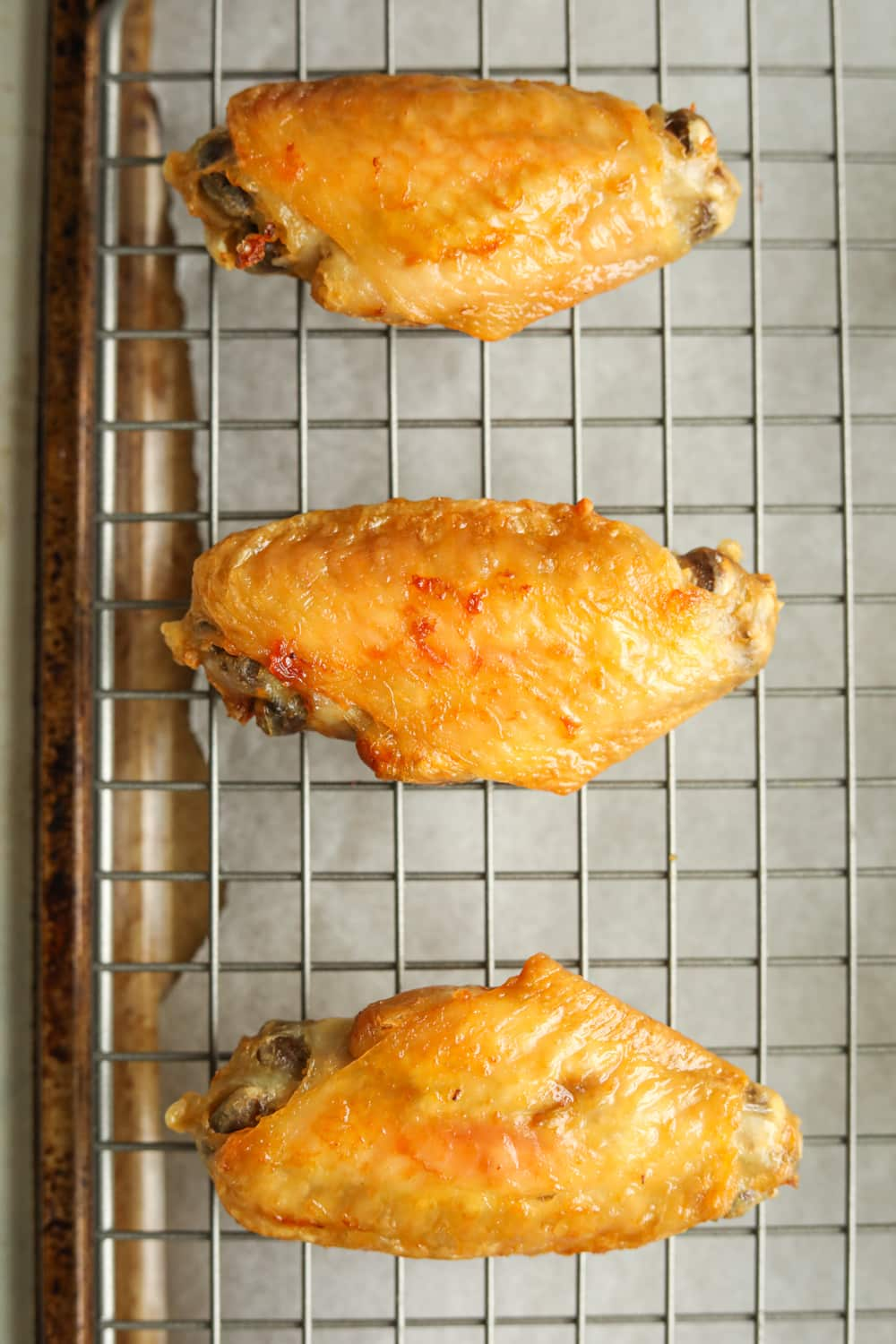 Cooked chicken wings on a wire rack.
