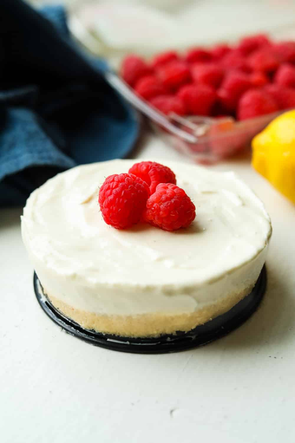 Cheesecake topped with cheesecake with raspberries and lemons set behind it.