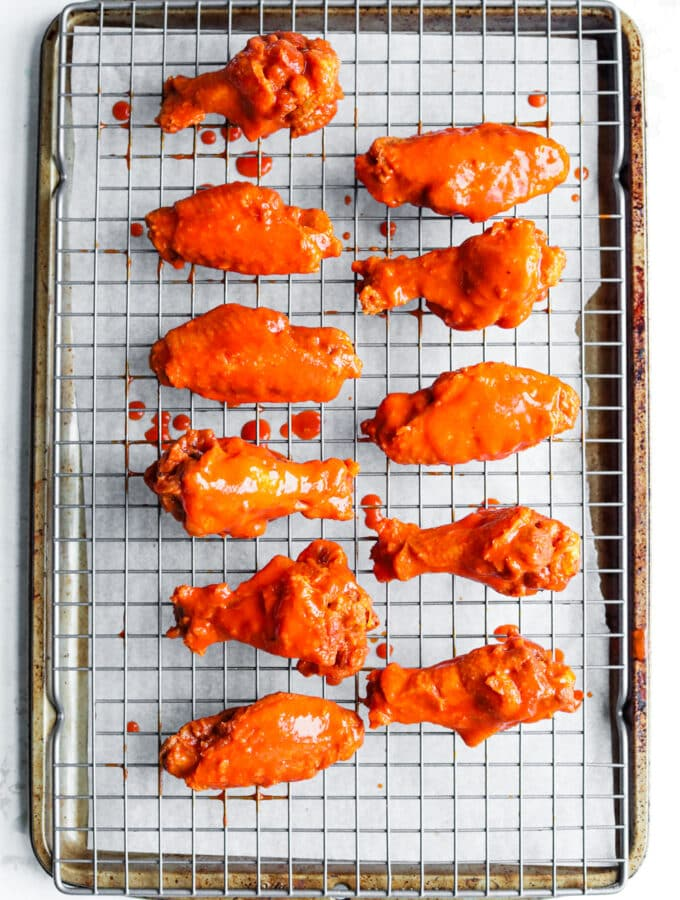 11 Chicken wings covered in hot sauce on a wire rack set over a baking sheet.