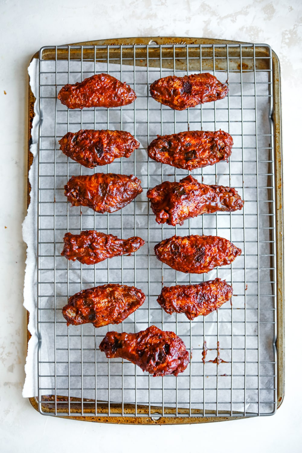 11 BBQ chicken wings on a drying rack that's set over a baking sheet.