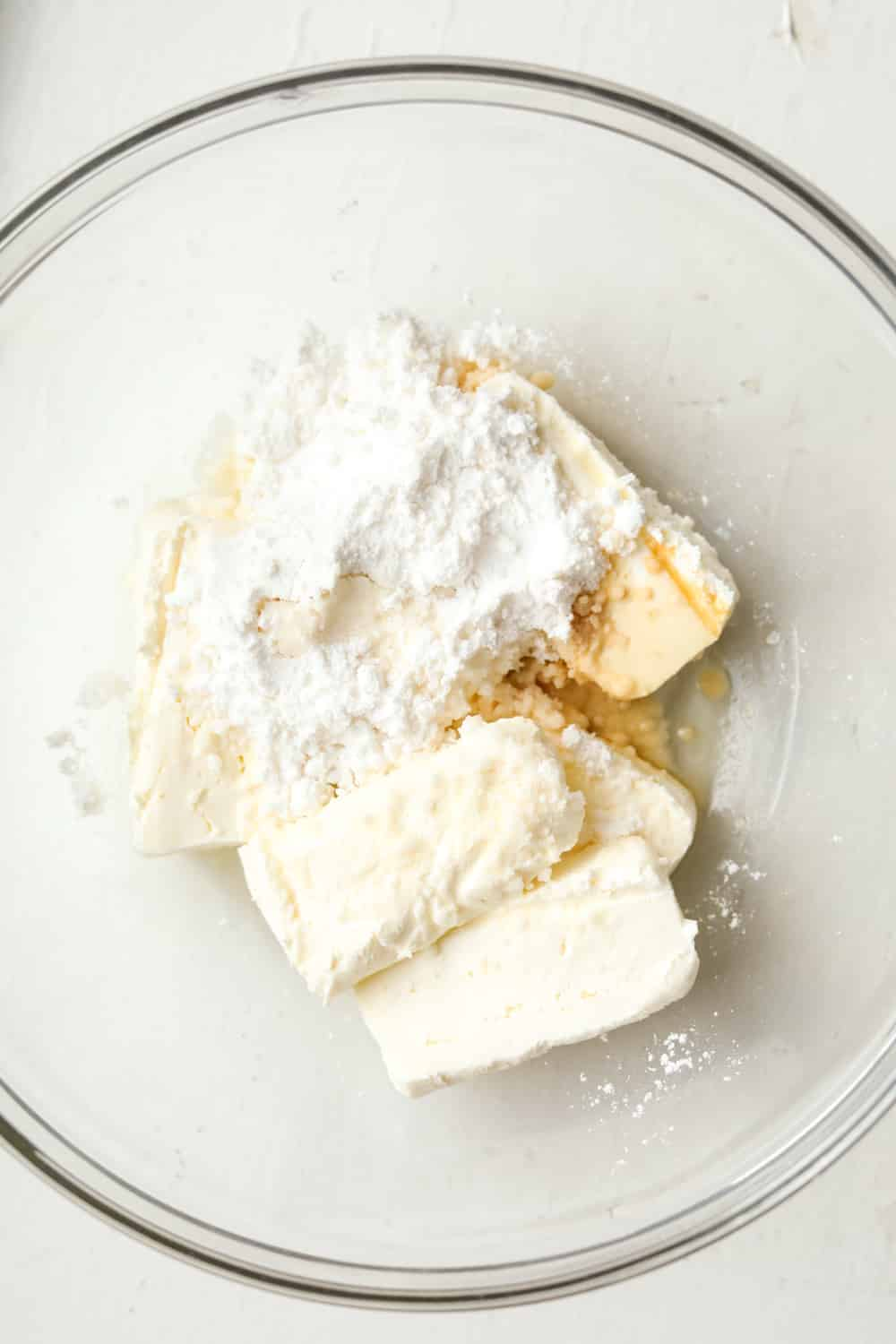 Cream cheese, sour cream, and other ingredients to make a filling for cheesecake in a glass bowl.