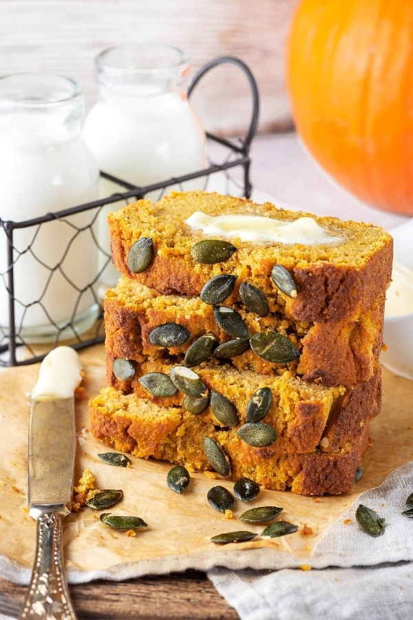 Four slices of pumpkin bread on top of one another in a stack on a piece of brown parchment paper on a gray tablecloth. There is a knife with butter on it to the left of the bread and behind it is a wire holder with two glass jars of milk in it. To the back right is part of a pumpkin.