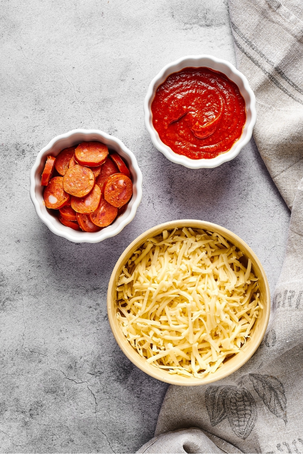 A bowl of shredded mozzarella cheese, a small white bowl of pepperoni, and a small white bowl of pizza sauce all on a grey counter.