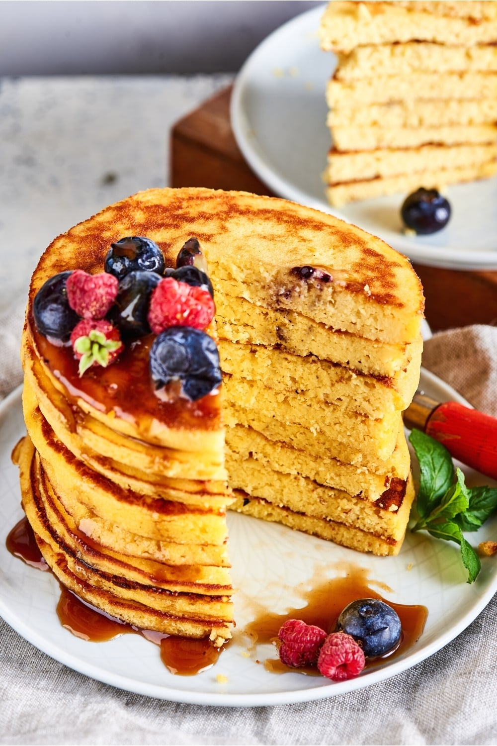 Eight cream cheese pancakes stacked on top of one another on a white plate. There is a triangle cut out of the pancakes and the inside of the pancake stack is showing.