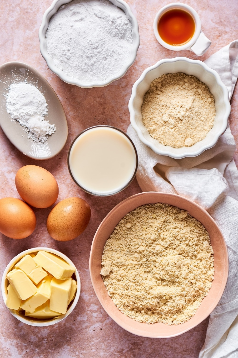 Ingredients for keto cake. There is a medium bowl with almond flour, a bowl with sticks of butter, three eggs in front of that, a cup of milk next to the eggs, a small bowl of coconut flour, a small bowl of vanilla extract, an oval dish of baking powder, and a small white dish of confectioner erythritol.