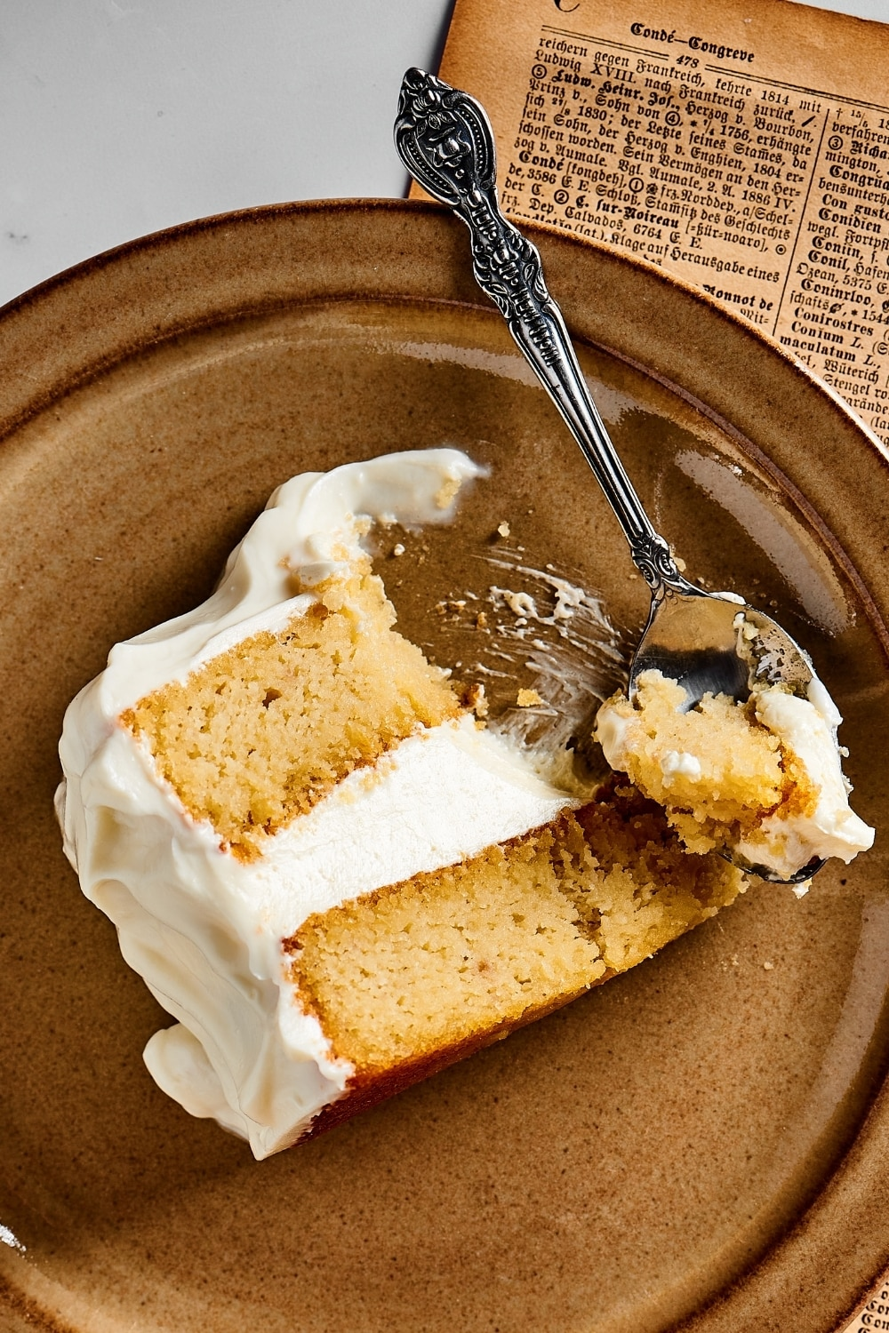 A slice of vanilla cake on top of a brown plate on a piece of newspaper. A spoon is rusting on the edge of the plate with the head of the spoon right next to the cake with a piece of it on it.