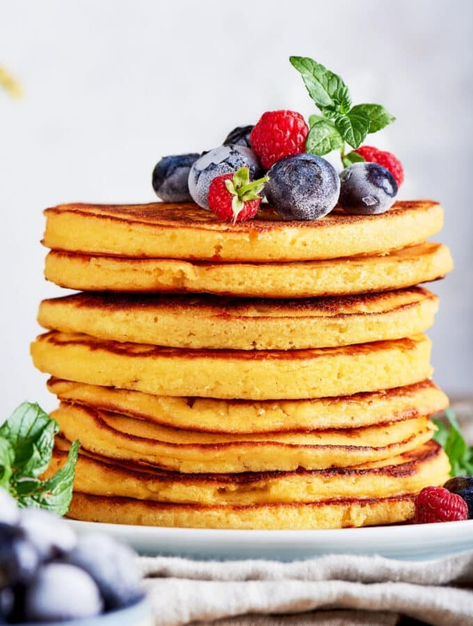 A stack of eight cream cheese pancakes on a white plate.