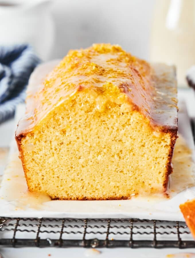 Pound cake loaf with a slice out of the front of it on a piece of parchment paper on a black wire rack.
