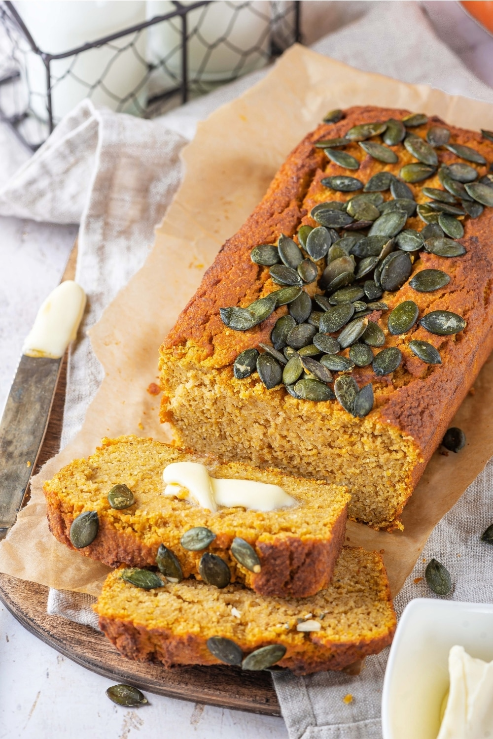 A loaf of pumpkin bread and a piece of parchment paper on a and a tablecloth that is on a wood board on the white counter. There are two slices of pumpkin bread line against one another in front of the loaf.
