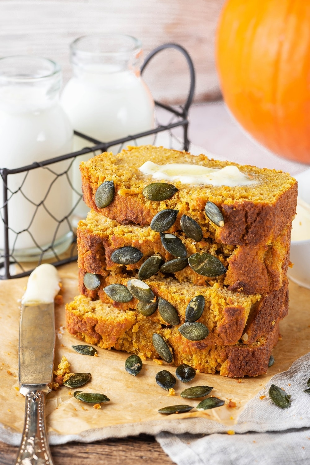 Four slices of pumpkin bread stack on top of one another on a piece of parchment paper on a gray table cloth. There are some pumpkin seeds in front of the slices and there is a knife to the left of them with butter on it. Behind the stack of pumpkin bread is of wire holder with two glass jars of milk.