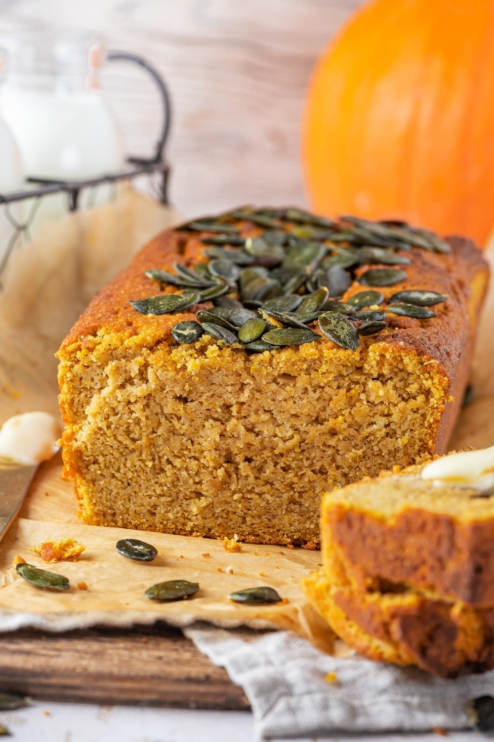 A pumpkin bread loaf on a piece of parchment paper on a wood board. There is part of two slices from the bread in front of it and there is part of a pumpkin behind it.