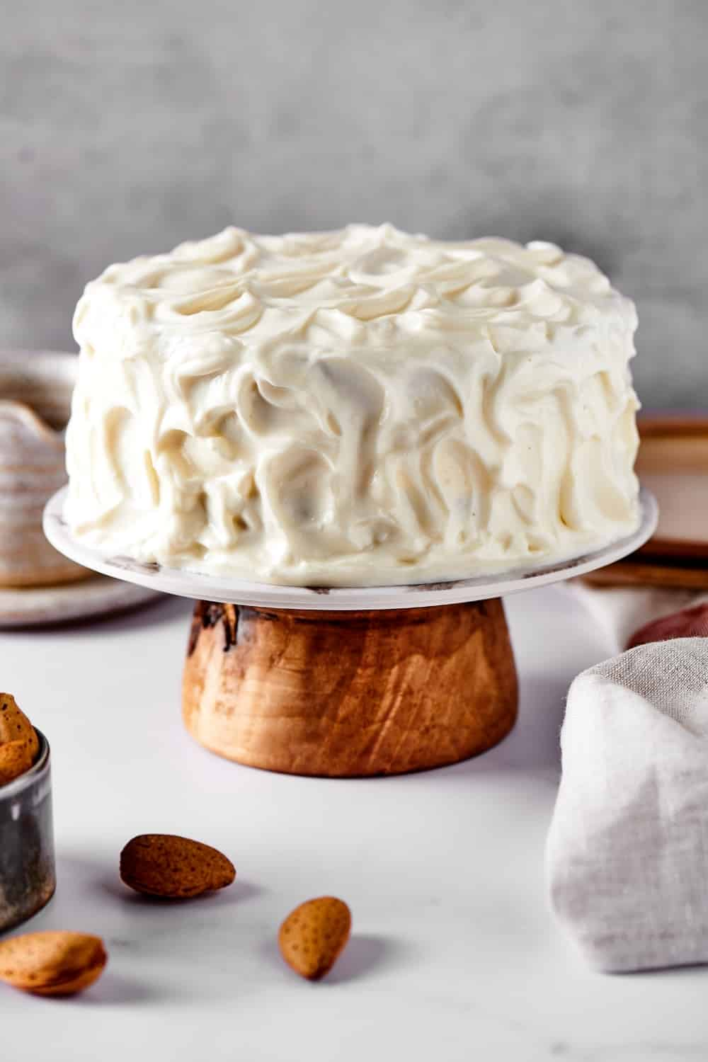 A vanilla cake covered in vanilla frosting on a cake stand and a white counter.