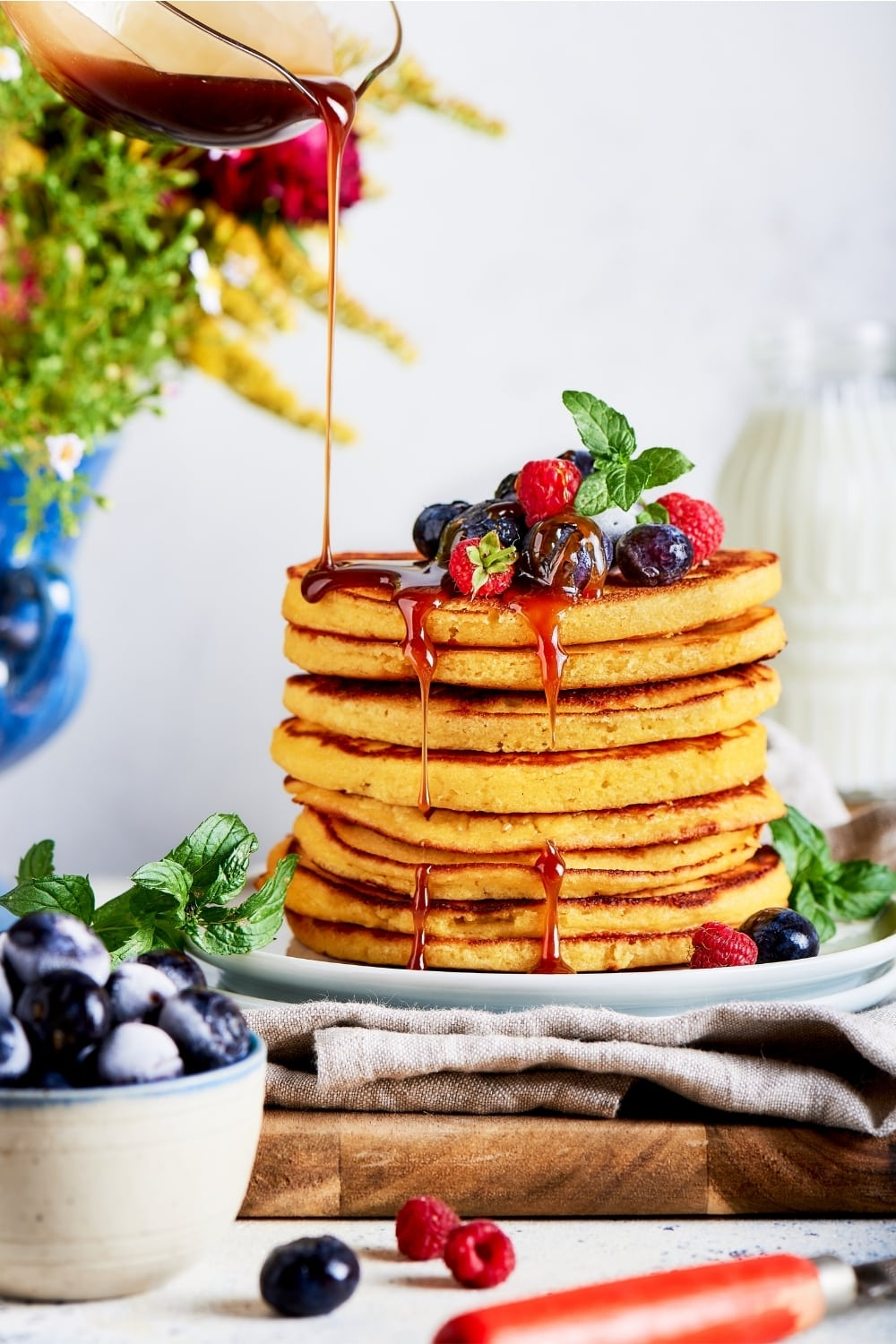 A cream cheese pancakes stacked on top of one another on a white plate that is on a gray tablecloth and a wooden cutting board and a white counter. A glass pitcher is drizzling syrup on top of the pancakes and there are a few blueberries and raspberries on the top pancake.