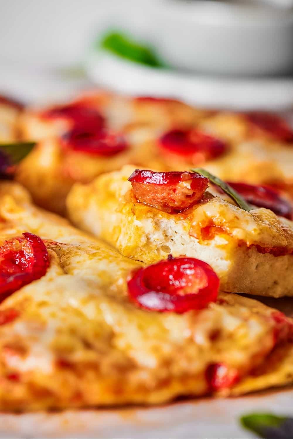A slice of cheese and pepperoni chicken crust pizza with a bite out of the front on top of another slice of pizza.