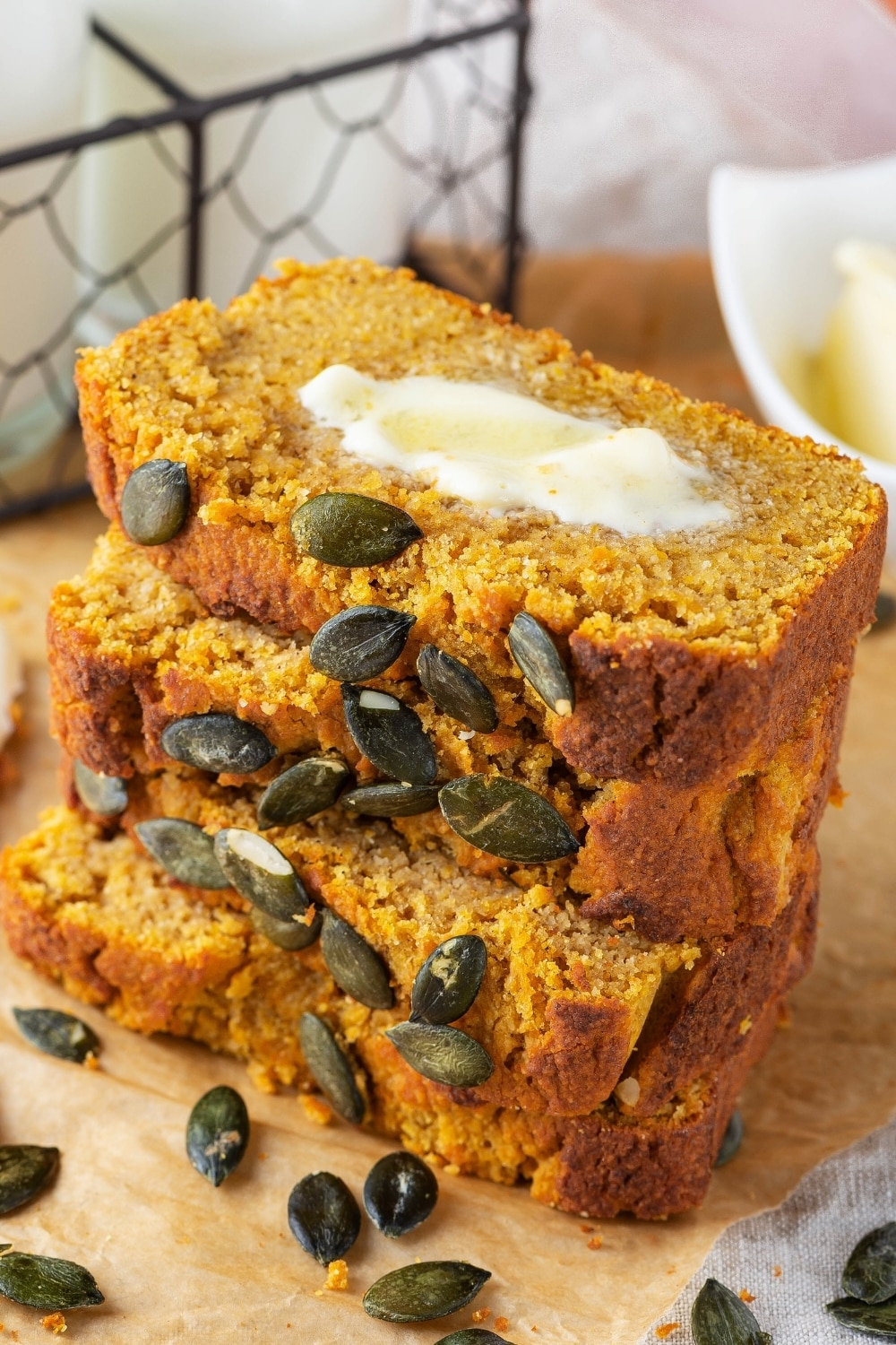 Four slices of pumpkin bread stacked on top of one another on a piece of parchment paper. The top slice has a slab of butter on it and pumpkin seeds in front of the bread.