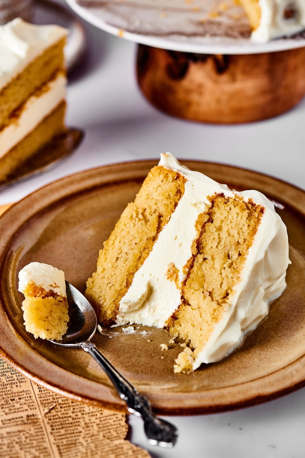 A slice of vanilla cake and a brown plate on a white counter. Hey spoons to the left of the piece of cake with part of the cake on it.
