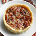 A pecan pie on a white plate.