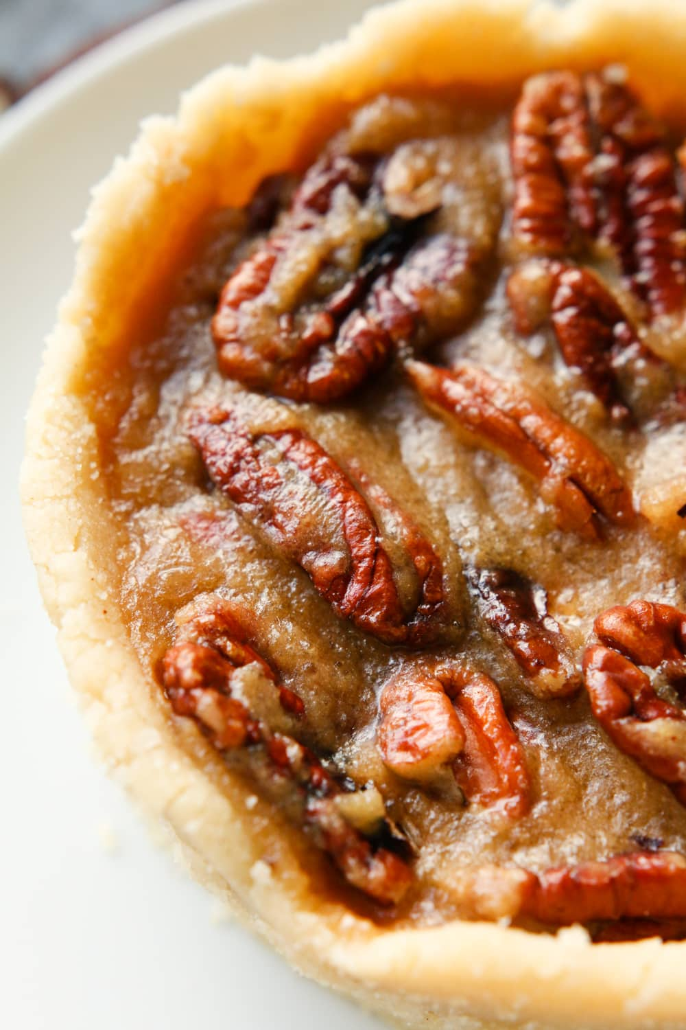 Half of a pecan pie on a white plate.