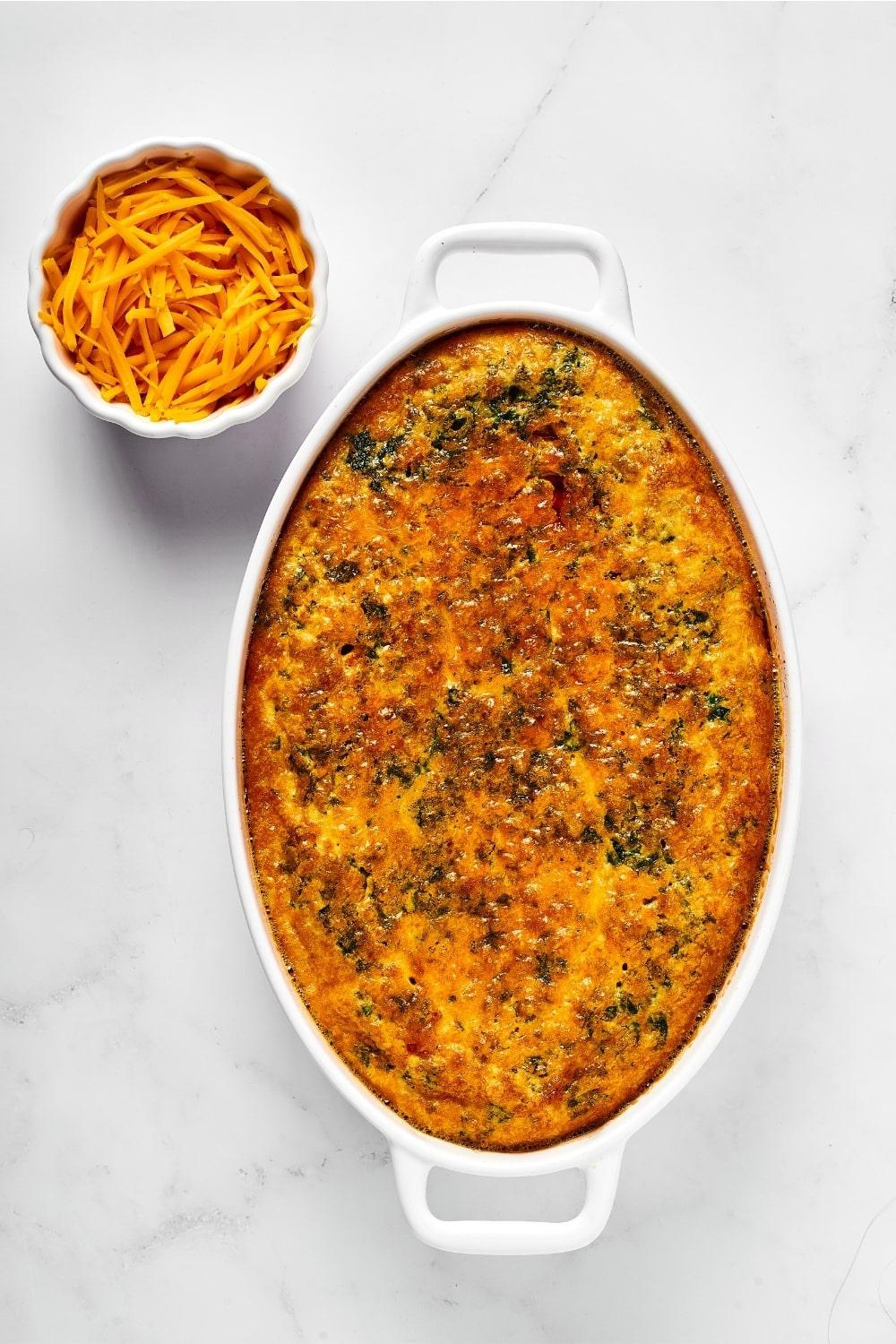 A breakfast casserole in a white casserole dish. At the back left of the dish is a small white bowl with shredded cheddar cheese in it.