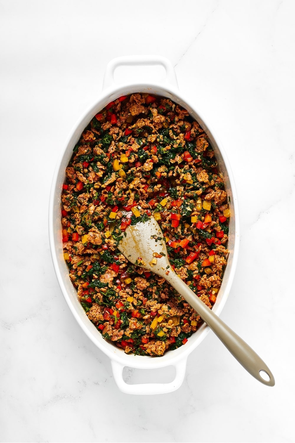 A white casserole dish filled with sausage crumbles, spinach, and yellow and red peppers. There is a spoon in the middle of it and the casserole dish is on a white counter.