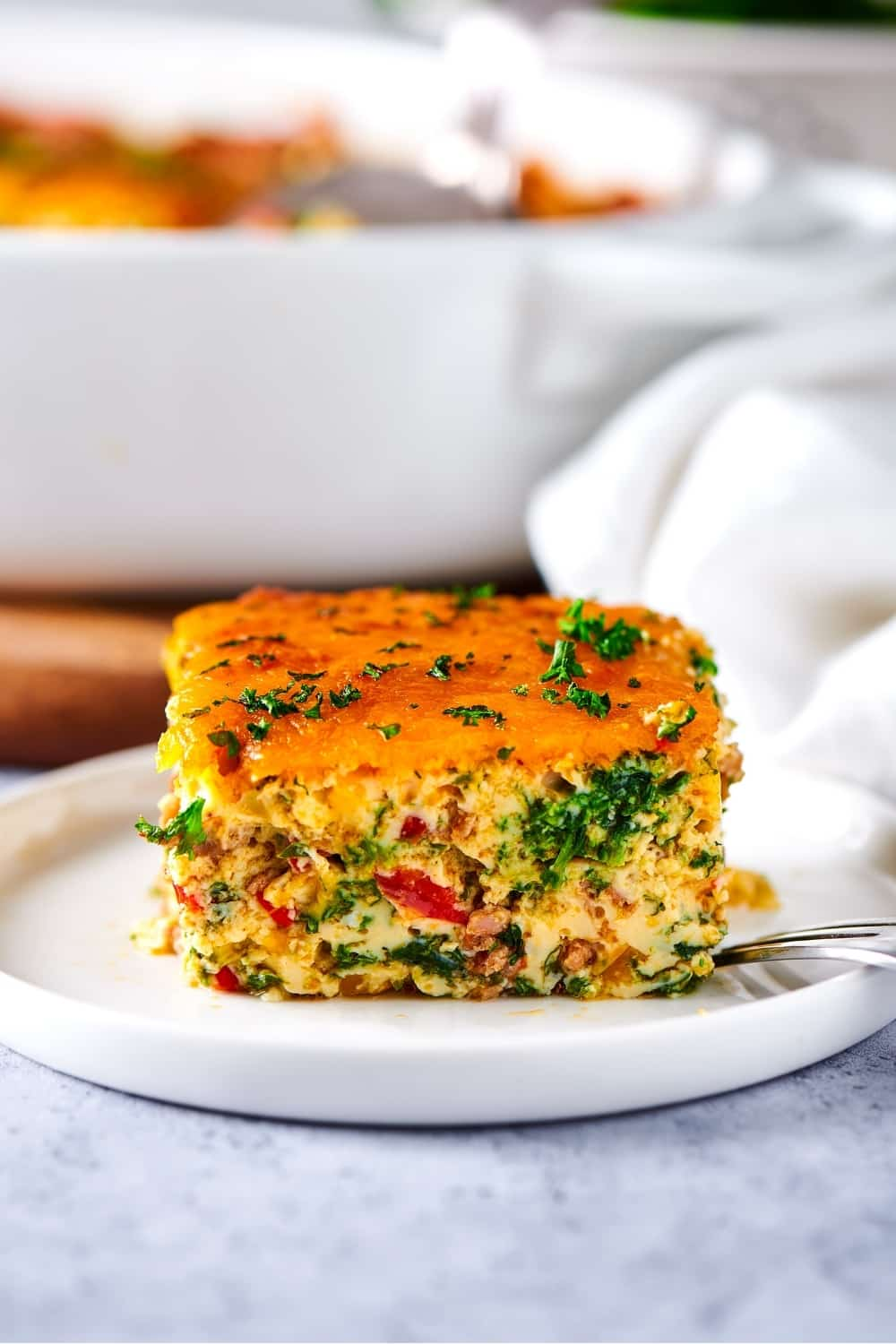 A square of breakfast casserole on top of a white plate on a gray counter.
