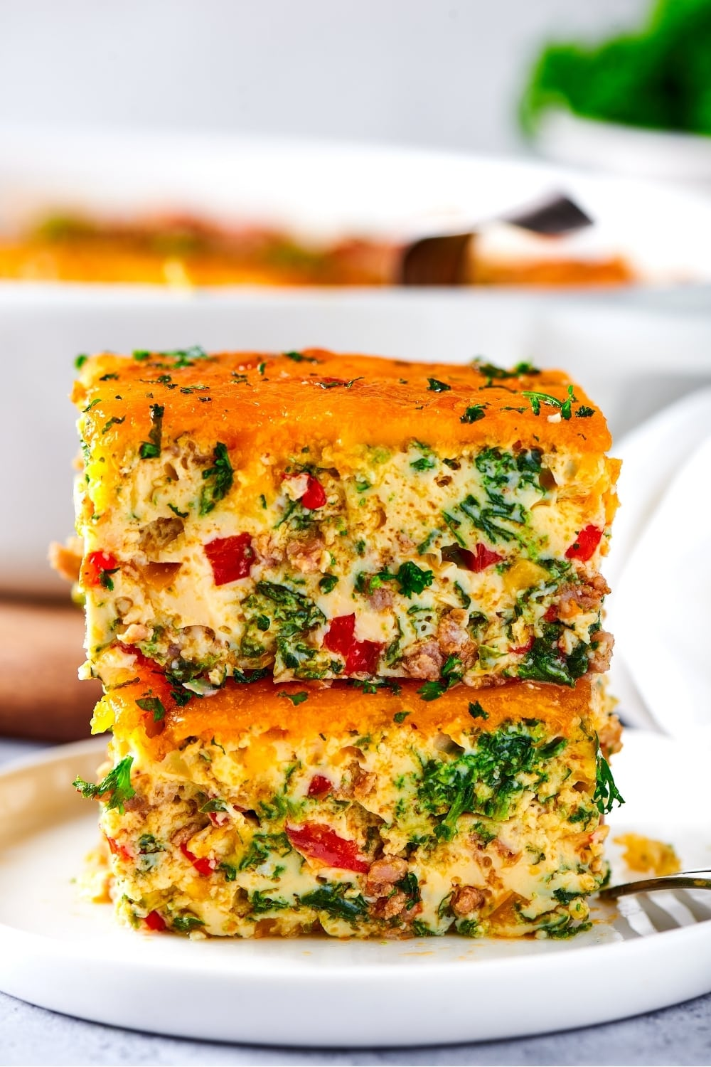 Two squares of breakfast casserole stacked on top of one another on a white plate.