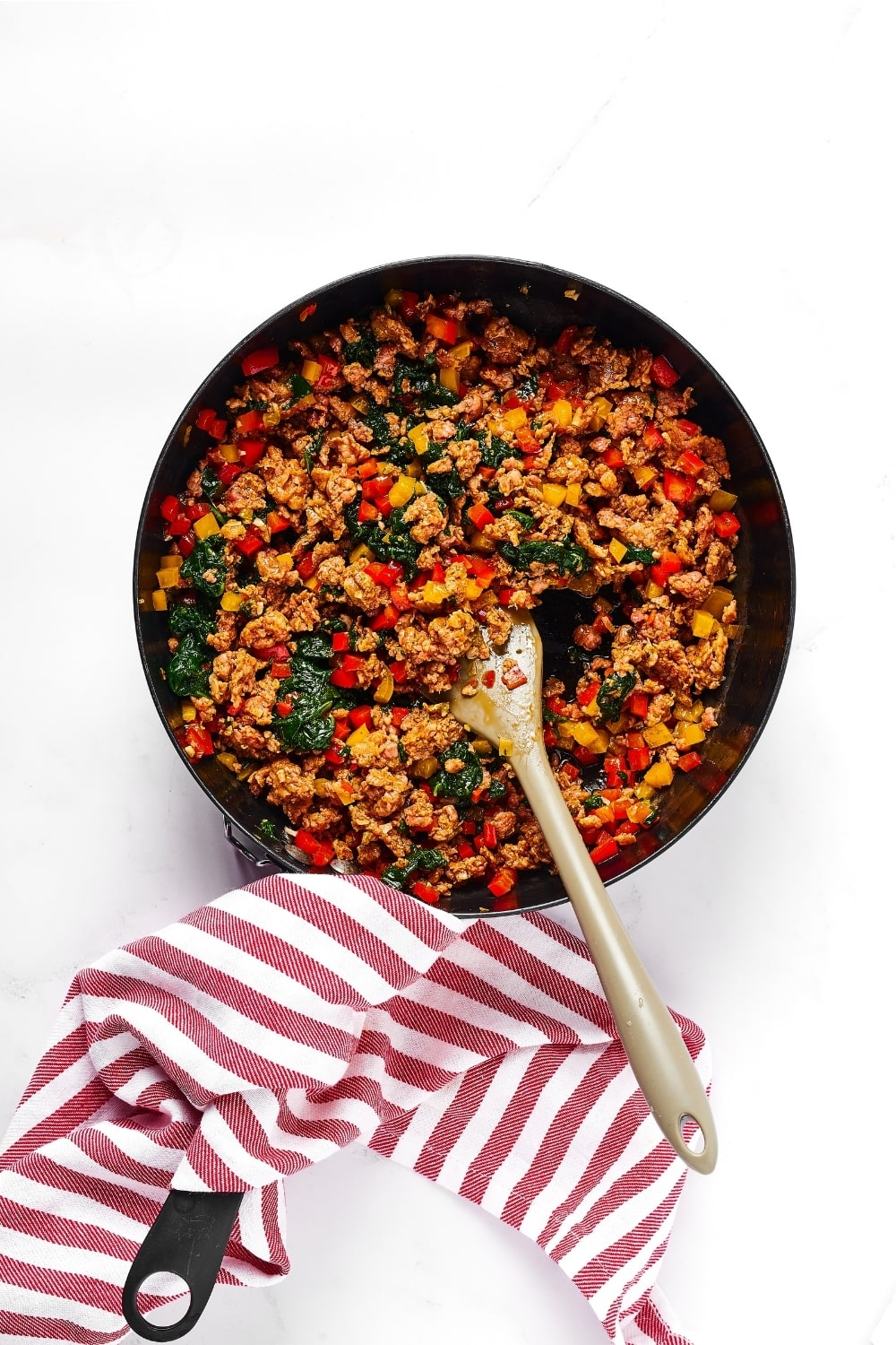 Black sauté pan with sausage crumbles, red and yellow peppers, and spinach with a wooden spoon in the middle of them. There is a red and white striped napkin on the handle.